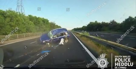 Dashcam video grab showing a blue Mini rolling over after colliding with a silver Ford Mondeo and crashing against the barrier on the M4 motorway near Port Talbot