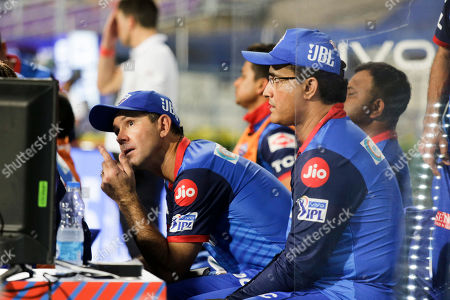 Former Australian cricket captain Ricky Ponting, left and former Indian cricket captain Sourav Ganguly, coach and mentor respectively to Delhi Capitals team watch the game on a TV set at dugout during the VIVO IPL cricket T20 match against in Kolkata, India