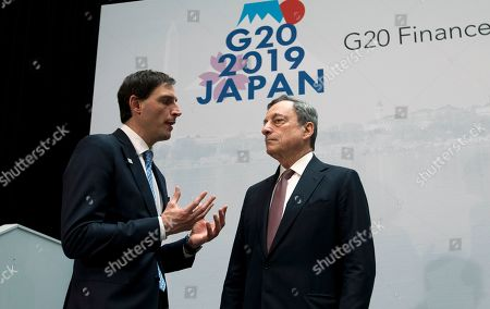 Netherlands' Finance Minister Wopke Hoekstra, left, speaks with the President of European Central Bank Mario Draghi, during a group photo of the G20 Finance Minister and Central Bank Governors at the World Bank/IMF Spring Meetings in Washington