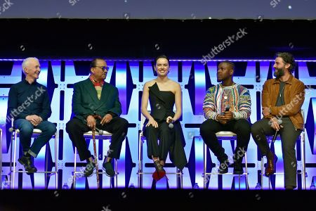 """Anthony Daniels, Billy Dee Williams, Daisy Ridley, John Boyega, Oscar Isaac. Anthony Daniels, from left, Billy Dee Williams, Daisy Ridley, John Boyega and Oscar Isaac participate in the """"Star Wars: The Rise of Skywalker"""" panel on day 1 of the Star Wars Celebration at Wintrust Arena, in Chicago"""