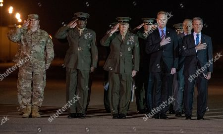 Front row, from left to right: United States Air Force Colonel Matthew Jones, 436th Airlift Wing, Vice Commander; Sergeant Major of the US Marine Corps Ronald Green; US Marine Corps General Robert B. Neller, Commandant of the Marine Corps; Acting United States Secretary of Defense Patrick M. Shanahan; and Governor John Carney (Democrat of Delaware); and US Senator Tom Carper (Democrat of Delaware), salute as a US Marine Corps carry team participates in the Dignified Transfer of the transfer case containing the remains of US Marine Corps Staff Sergeant Christopher A. Slutman at Dover Air Force Base