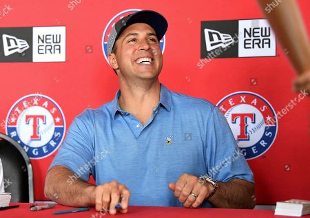 Stock Picture of Former Texas Rangers first baseman Mark Teixeira signs autographs before a baseball game between the Rangers and the Oakland Athletics, in Arlington, Texas