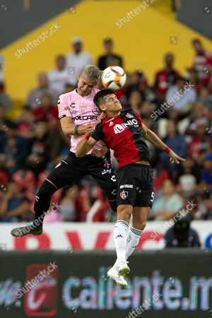 Atlas' Anderson Santamaria (R) vies for the ball with Necaxa's Alexis Pena (L) during the Mexican tournament soccer match between Atlas and Necaxa at Jalisco stadium in Guadalajara, Mexico, 12 April 2019.