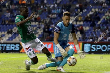 Puebla's goalkeeper Nicolas Vikonis (R) vies for the ball against Leon's Joel Campbell (L) during a match of the Mexican Tournament between Puebla and Leon at the Cuauhtemoc stadium in Puebla, Mexico, 12 April 2019.