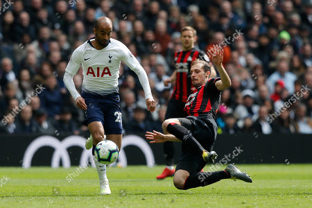 Tottenham's Lucas Moura, left, is tackled by Huddersfield's Erik Durm as runs with the ball during the English Premier League soccer match between Tottenham Hotspur and Huddersfield Town at Tottenham Hotspur stadium in London
