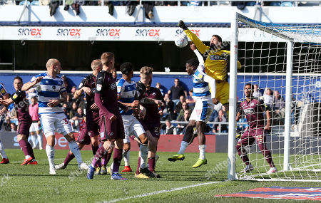 Stock Picture of Kristoffer Nordfeldt goalkeeper of Swansea City  punches clear as Bright Osayi-Samuel of QPR  challenges