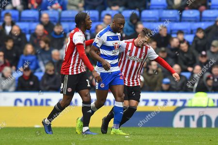 Stock Picture of Romaine Sawyers (19) of Brentford and Sergi Canos (7) of Brentford don't like how fast Yakou Meite (21) of Reading is taking to leave the field after being subsituted and try to hurry him up during the EFL Sky Bet Championship match between Reading and Brentford at the Madejski Stadium, Reading