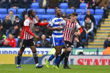 Stock Photo of Romaine Sawyers (19) of Brentford and Sergi Canos (7) of Brentford don't like how fast Yakou Meite (21) of Reading is taking to leave the field after being subsituted and try to hurry him up during the EFL Sky Bet Championship match between Reading and Brentford at the Madejski Stadium, Reading