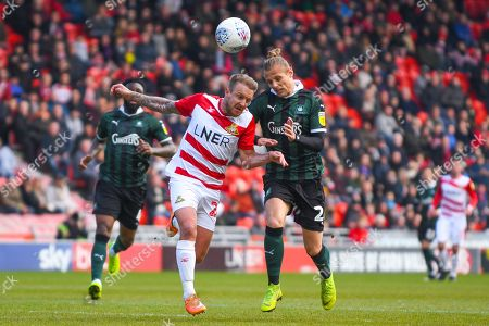 James Coppinger of Doncaster Rovers (26) and Oscar Threlkeld of Plymouth Argyle (26) in action during the EFL Sky Bet League 1 match between Doncaster Rovers and Plymouth Argyle at the Keepmoat Stadium, Doncaster