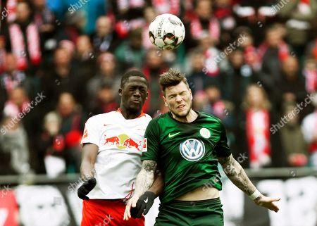 Wolfsburg's Daniel Ginczek, right, challenges for the ball against Leipzig's Ibrahima Konate, left, during the German Bundesliga soccer match between RB Leipzig and VfL Wolfsburg in Leipzig, Germany