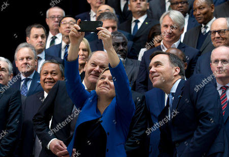 Swedish Finance Minister Magdalena Andersson take a selfie with German Finance Minister Olaf Scholz, left, and Canada Finance Minister William Morneau, right, during the International Monetary Fund IMF Governors group photo at the World Bank/IMF Spring Meetings in Washington