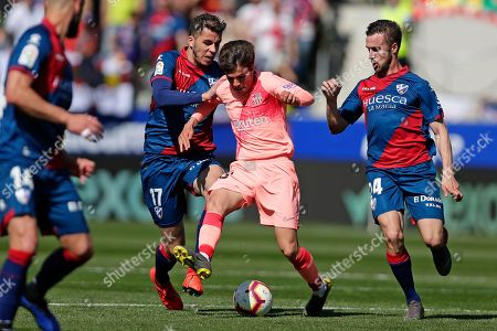 Barcelona's Riqui Puig, center, vies for the ball with Huesca's Christian Rivera, left, and Jorge Miramon during the Spanish La Liga soccer match between Huesca and Barcelona at the Alcoraz stadium in Huesca