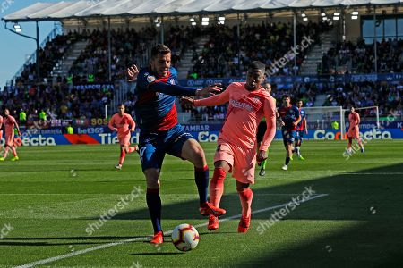 Stock Photo of Barcelona's Malcom Oliveira, right, and Huesca's Christian Rivera battle for the ball during the Spanish La Liga soccer match between Huesca and Barcelona at the Alcoraz stadium in Huesca