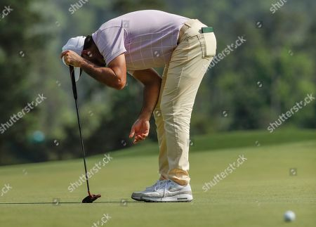Jason Day, of Australia, reacts to a putt on the eighth hole during the third round for the Masters golf tournament, in Augusta, Ga