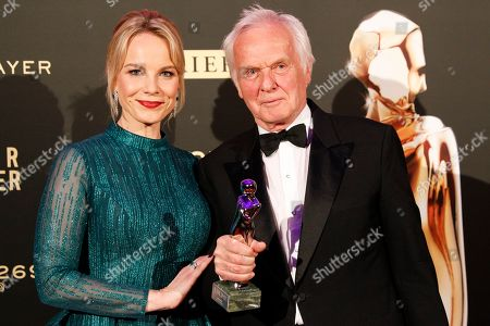 TV producer Jan Mojto (R) poses with Romy award for the Platinum Romy award for his life's work next to Latvian mezzo-soprano Elina Garanca (L) during the Romy Gala television award ceremony at the Hofburg palace in Vienna, 13 April 2019.