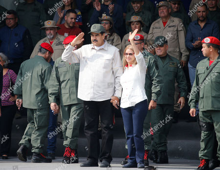 Venezuela's President Nicolas Maduro, left, and his wife Cilia Flores lead the tenth anniversary celebration of the Bolivarian Militia in Caracas, Venezuela, . Officially known as the Venezuelan National Bolivarian Militia, it is a branch of the National Armed Forces of Venezuela created by the late President Hugo Chavez