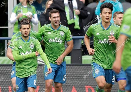 Seattle Sounders forward Will Bruin, center, walks with teammates Victor Rodriguez, left, and Kim Kee-Hee, right, after Bruin scored a goal against Toronto FC during the first half of an MLS soccer match, in Seattle