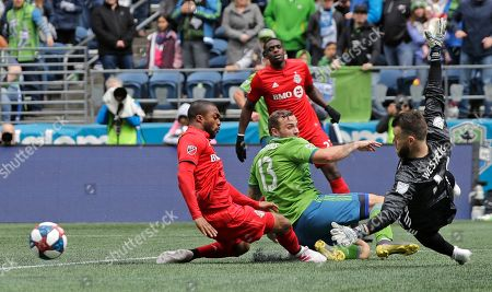 Toronto FC goalkeeper Quentin Westberg, right, watches the ball after Seattle Sounders forward Jordan Morris (13) couldn't get to a cross under pressure from Toronto FC's Ashtone Morgan, left, and Chris Mavinga, second from right, during the second half of an MLS soccer match, in Seattle. The Sounders won 3-2