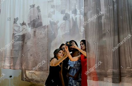 Young Cubans take a picture with a work of art from Carrie Mae Weems, a New York-based American artist during the opening of an exhibition of her and other young U.S. artists in Havana, Cuba, . American and international artists have flocked to Havana's Bienal, an art show designed to showcase new works and foster an appreciation of art among the public, while giving new artists a venue to display their work