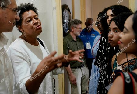 Carrie Mae Weems, second from left, a New York-based American artist, talks with other young artists during the opening of an exhibition in Havana, Cuba, . American and international artists have flocked to Havana's Bienal, an art show designed to showcase new works and foster an appreciation of art among the public, while giving new artists a venue to display their work