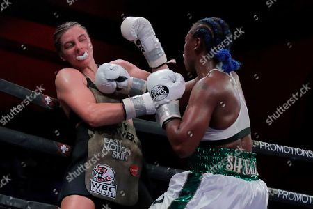 Claressa Shields, right, punches the mouthpiece out of Christina Hammer's mouth during the eighth round of the women's middleweight championship boxing bout, in Atlantic City, N.J. Shields won by unanimous decision