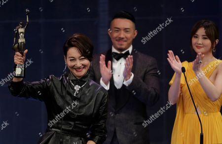 "Hong Kong actress Kara Wai raises the trophy after winning the Best Supporting Actress of her movie ""Tracey"" at the Hong Kong Film Awards in Hong Kong"
