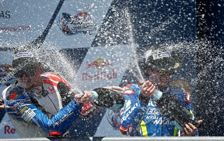 Team Suzuki Ecstar Team rider Alex Rins of Spain (R) sprays champagne on Alma Pramac Racing Team rider Jack Miller of Australia (L) on the podium after finishing second in the MotoGP Race at the Red Bull Grand Prix of the Americas at Circuit of the Americas in Austin, Texas, USA, 14 April 2019.