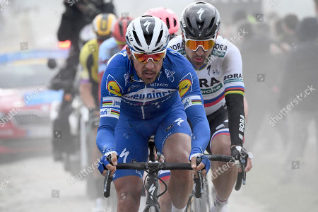 Deceuninck Quick Step team rider Philippe Gilbert (L) of Belgium and Bora Hansgrohe team rider Peter Sagan (R) of Slovakia in action on a cobblestone section during the 117th Paris Roubaix cycling race, France, 14 April 2019.