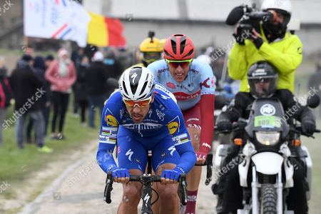 Deceuninck Quick Step team rider Philippe Gilbert (L) of Belgium and Team Katusha Alpecin Nils Politt (R) of Germany in action on a cobblestone section during the 117th Paris Roubaix cycling race, France, 14 April 2019.