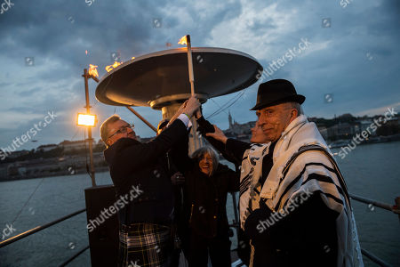 (L-R) British Secretary of State for Scotland David Mundell, five-times Olympic champion gymnast and Holokaust survivor Agnes Keleti and Chief Rabbi Peter Kardos light a torch during the 17th March of the Living commemoration held for the Hungarian victims of the Holocaust in downtown Budapest, Hungary, 14 April 2019.
