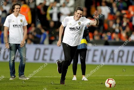 British actors James Phelps (L) and his brother Oliver Phelps (R) participate in the kick off shot before the Spanish LaLiga soccer match between Valencia CF and UD Levante at Mestalla stadium, Valencia, eastern Spain, 14 April 2019.