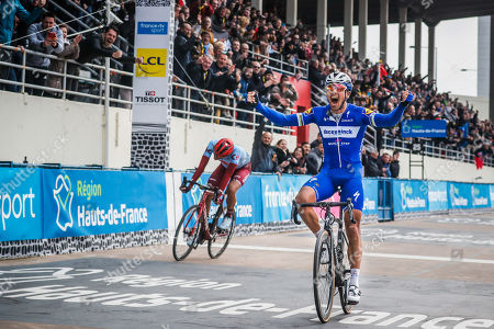 Deceuninck Quick Step team rider Philippe Gilbert (C) of Belgium celebrates his win as he crosses the finish line of the 117th Paris Roubaix cycling race, France, 14 April 2019. Team Katusha Alpecin Nils Politt (L) finishes with second position.