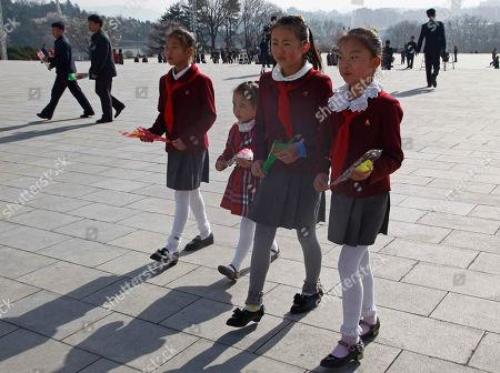 Children carry flowers to pay tribute to the statues of former leaders Kim Il Sung and Kim Jong Il on Mansu Hill to mark the Day of the Sun in Pyongyang