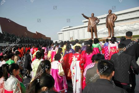 People carry flowers to pay tribute to the statues of former leaders Kim Il Sung and Kim Jong Il on Mansu Hill to mark the Day of the Sun in Pyongyang