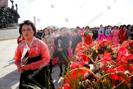 People visit to pay tribute to the statues of former leaders Kim Il Sung and Kim Jong Il on Mansu Hill to mark the Day of the Sun in Pyongyang