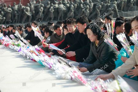 People pay tribute to the statues of former leaders Kim Il Sung and Kim Jong Il on Mansu Hill to mark the Day of the Sun in Pyongyang