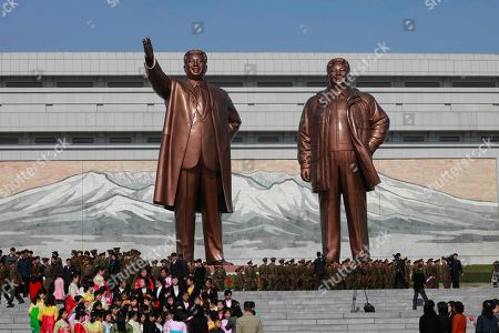 People pay tribute to the statues of former leaders Kim Il Sung, left, and Kim Jong Il on Mansu Hill to mark the Day of the Sun in Pyongyang