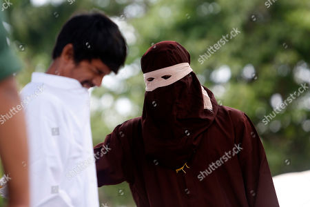 An executioner, known as 'algojo', punishes a person (R) by public caning after they broke Sharia for having sexual relations outside of wedlock in Banda Aceh, Aceh, Indonesia, 15 April 2019. Aceh is the only Indonesian province that has implemented Sharia law.