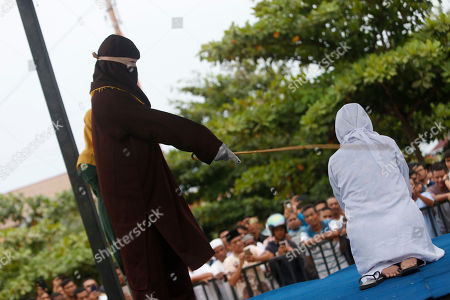 An executioner, known as 'algojo', punishes an Acehnese woman (R) by public caning after she broke Sharia for having sexual relations outside of wedlock in Banda Aceh, Aceh, Indonesia, 15 April 2019. Aceh is the only Indonesian province that has implemented Sharia law.