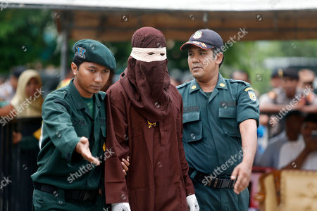 An executioner (C), known as 'algojo', prepares to punishes an Acehnese person by public caning after she broke Sharia for having sexual relations outside of wedlock in Banda Aceh, Aceh, Indonesia, 15 April 2019. Aceh is the only Indonesian province that has implemented Sharia law.