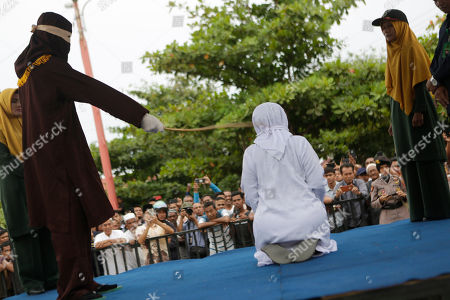 An executioner, known as 'algojo', punishes a an Acehnese woman (C) by public caning after she broke Sharia for having sexual relations outside of wedlock in Banda Aceh, Aceh, Indonesia, 15 April 2019. Aceh is the only Indonesian province that has implemented Sharia law.