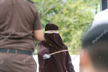 An executioner, known as 'algojo', punishes a person (C) by public caning after they broke Sharia for having sexual relations outside of wedlock in Banda Aceh, Aceh, Indonesia, 15 April 2019. Aceh is the only Indonesian province that has implemented Sharia law.