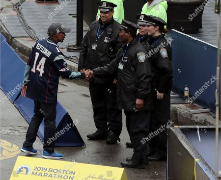 Stock Picture of Grand marshall and 2014 Boston Marathon champion Meb Keflezighi, left, of San Diego, shakes hands with Boston police officers before the start of the 123rd Boston Marathon, in Boston