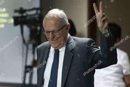 Peru's former President Pedro Pablo Kuczynski flashes a vee for victory as he returns to a court hearing to determine his release, in Lima, Peru, . A judge in Peru ordered last week the detention for 10 days of the former leader as part of a money laundering probe into his consulting work for the company at the heart of Latin America's biggest graft scandal