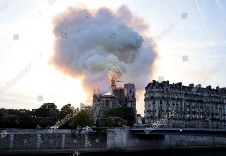 Flames and smoke rise as the spire on Notre Dame cathedral collapses in Paris, . Massive plumes of yellow brown smoke is filling the air above Notre Dame Cathedral and ash is falling on tourists and others around the island that marks the center of Paris