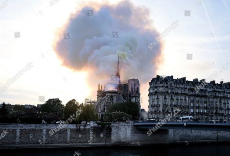 Stock Picture of Flames and smoke rise as the spire on Notre Dame cathedral starts to collapse in Paris, . Massive plumes of yellow brown smoke is filling the air above Notre Dame Cathedral and ash is falling on tourists and others around the island that marks the center of Paris