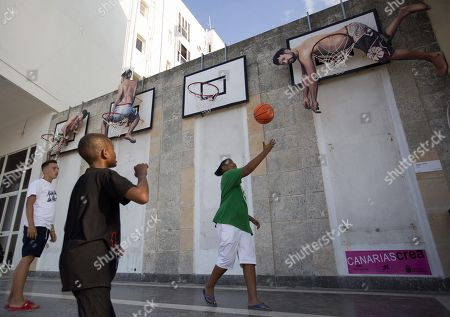 People play basketball in the artistic installation 'Basket People' by Spanish artists Martin and Sicilia, which is part of the project Detras del Muro (Behind the Wall), in Havana, Cuba, 14 April 2019 (issued 16 April). The XIII Biennial of Havana, the largest event in the visual arts in the country, officially began in the country's capital, transforming the city for a month, into the largest gallery in the world with streets, facades, parks and buildings 'intervened' for more than 300 artists from 52 countries.