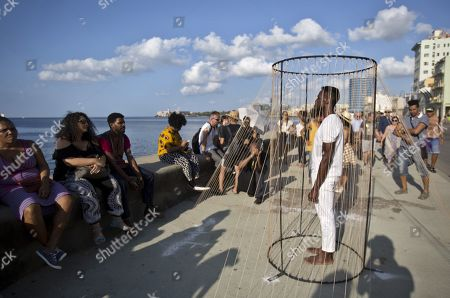 People watch the installation for the project Detrás del Muro (Behind the Wall) by Cuban artist Carlos Martiel (R) in Havana, Cuba, 14 April 2019 (issued 16 April 2019). The 13th Havana Biennial runs from 12 April until 12 May.