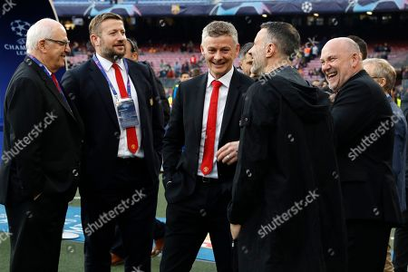 Manchester United coach Ole Gunnar Solskjaer, center, speaks with Former Manchester United player Ryan Giggs, second right and his assistant manager Mike Phelan, right, on the pitch ahead of the Champions League quarterfinal, second leg, soccer match between FC Barcelona and Manchester United at the Camp Nou stadium in Barcelona, Spain