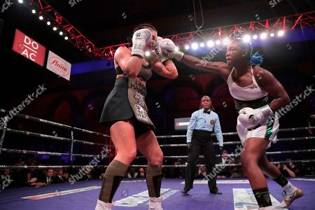 Claressa Shields, right, fights Christina Hammer during the fourth round of a women's unification world middleweight championship bout, in Atlantic City, N.J